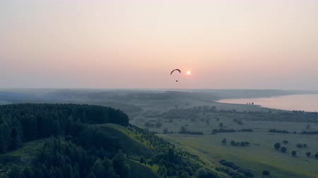 скольжение : Sunlit scenery and an airsailing vehicle drifting high above it. Paraglider in the sky