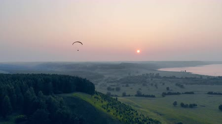 paracadutista : Ram-air parachute is drifting in the sky while the sun is setting