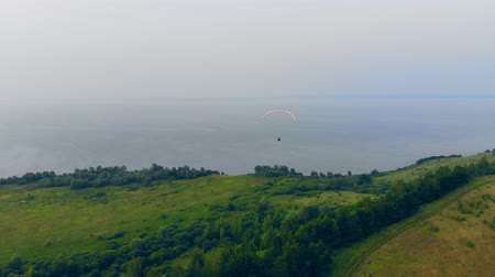 padák : Paraplane is sailing above the field towards the water. Parachute, paragliding comcept. Dostupné videozáznamy