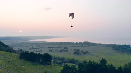 paracaidismo : A person on a parawing is gliding above the green landscape Archivo de Video