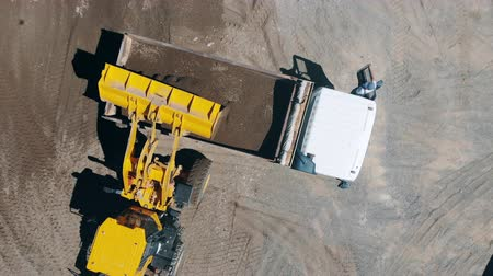 equipamento : An excavator and a truck are transporting pounded rocks in a top view