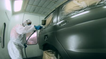 pneumatic : Male technician is colouring a car in the garage. Industrial spray painting process.