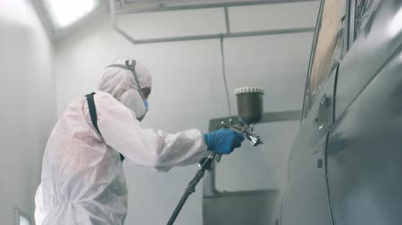 dyeing : Male worker is colouring the automobile with the airbrush. Industrial spray painting process.
