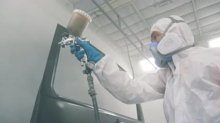 pneumatic : Serviceman is using the painting nozzle to colour the car. Industrial spray painting process.