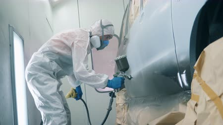 aerografo : Metallic colour is getting sprayed onto the car by the serviceman