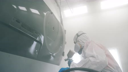 pneumatic : Cars door is getting spray-coloured by the garage worker. Industrial spray painting process.