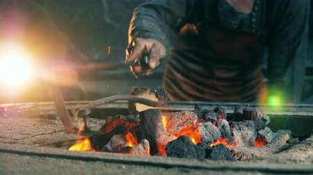 coal fired : A man moves coal in fire, working at a forge. Stock Footage
