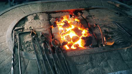 kowalstwo : Smithing tools lying near a fire at a forge.