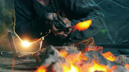 licenziato : Person heats a knife on fire while working at a forge.