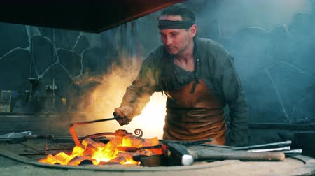 licenziato : Male blacksmith uses a metal poker to move coal. Blacksmith forging iron in workshop.