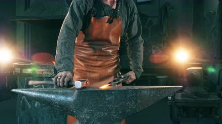 kowalstwo : A blacksmith hammers a hot knife on anvil.