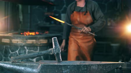 scenes : Man hits a knife with a hammer, working at a forge. Blacksmith forging molten metal