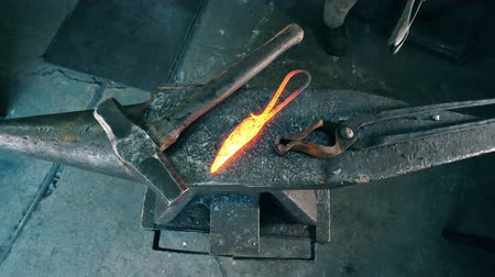 kowalstwo : Professional blacksmith puts hot knife on anvil at a forge.