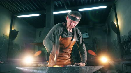 ручная работа : One blacksmith uses a hammer while working with knife at a forge. Стоковые видеозаписи
