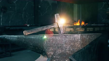 ручная работа : A big hammer on anvil at a forge.
