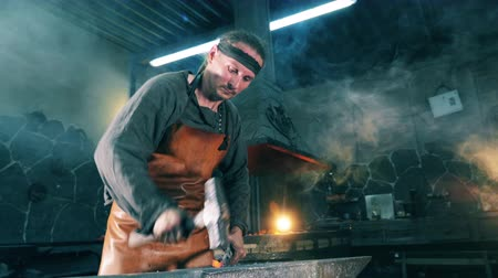 kowalstwo : Man hits a metal knife with a hammer while working at a forge. Wideo