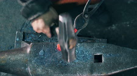 smithy : Working blacksmith hits a metal knife with a hammer on anvil.