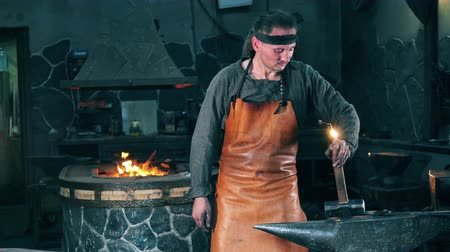 coal fired : Male forger stands near an anvil, holding a hammer. Blacksmith forging iron in workshop.
