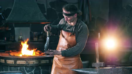 kowalstwo : Professional blacksmith looks at a metal knife, standing at a forge.