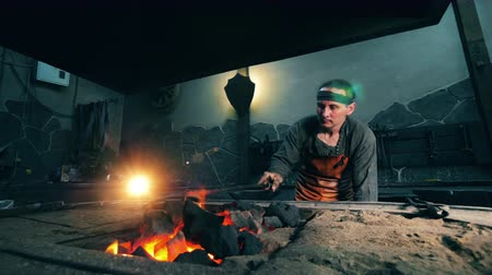 metal işi : One man moves coal in fire with metal poker. Blacksmith forging iron in workshop. Stok Video
