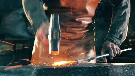 smithy : A forger hits hot knife with a metal hammer. Blacksmith forging iron in workshop.