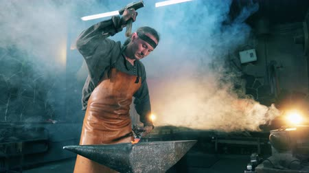 kowalstwo : Person uses hammer to hit a hot knife at a forge. Blacksmith forging molten metal