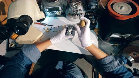 moersleutel : Jeweler, goldsmith in a professional jewelry workshop uses a wrench, working with a gold ring at a jewellery workshop.