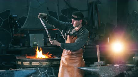 licenziato : Professional blacksmith examines a metal knife, standing at a forge.