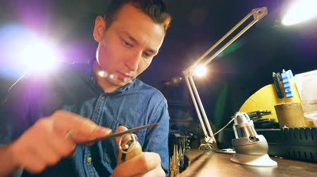 pertavsız : Jeweler, goldsmith in a professional jewelry workshop files down a metal ring while working at a jewellery workshop.