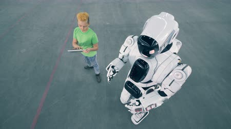 bot : One robot moves while a boy controls. Futuristic humanoid robot Stock Footage