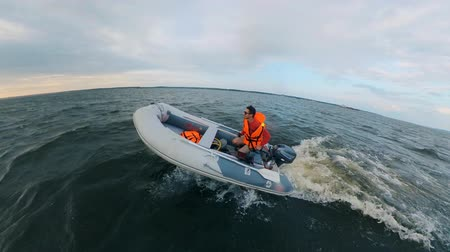tiller : A man in a life vest is driving a powerboat