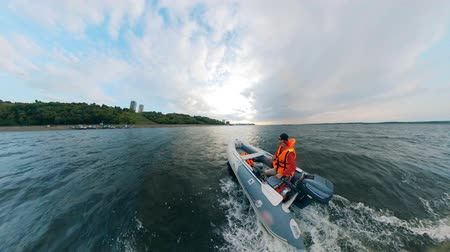 tiller : A man is sailing in an inflatable vessel along the coast