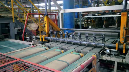 taş işçiliği : Freshly-made bricks are moving along the conveyor and getting cut
