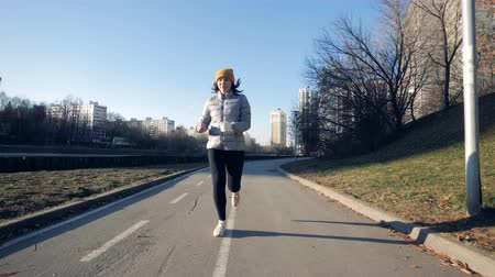 amputee : A woman with prosthetic hand jogging, close up.