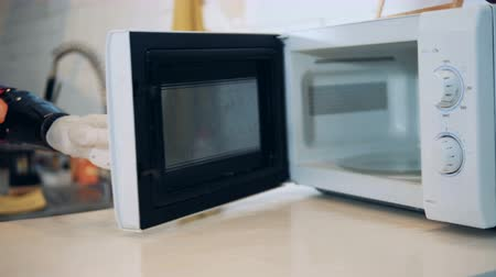 use computer : Handicapped woman with hand prosthesis works with a microwave, close up. Stock Footage