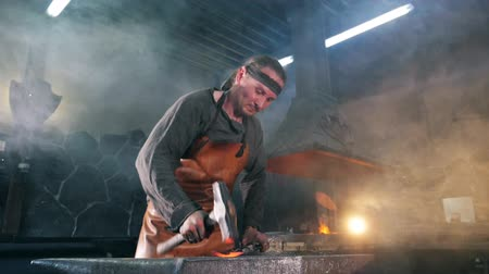 inflamed : Male forger is striking metal with a hammer in slow motion