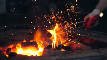 inflamed : Burning coals are getting beaten with the tongs Stock Footage