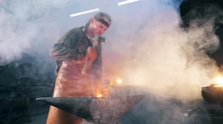 inflamed : Iron forging process held by the blacksmith. Slow motion.