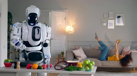 робот : Cyborg and human concept. Droid cooks dinner while a girl having fun.