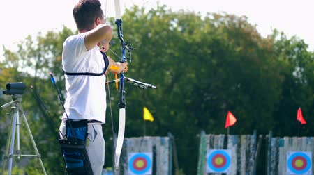 tiro com arco : One man aims at a target, shooting a bow.