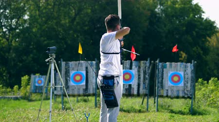 okçuluk : Man shoots a bow on a range with targets.