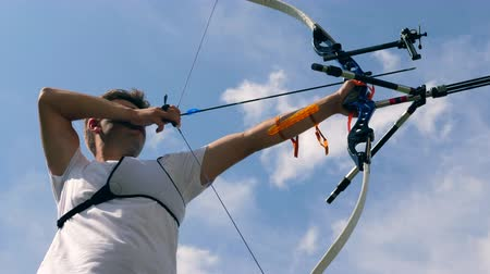 アーチェリー : Male archer training with a bow on a shooting range.