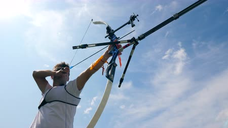 tiro com arco : Athlete strings a bow while practicing on a shooting range.