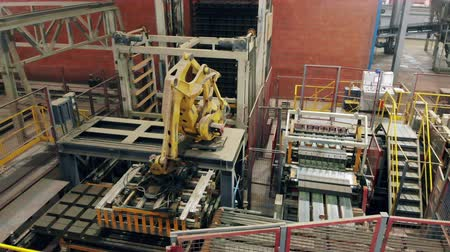 brick factory : Industrial robotic arm works with bricks, putting them on a conveyor.