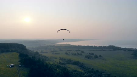 parachuting : A person is flying above the fields on the parafoil Stock Footage