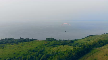 padák : A person in the paraglider is flying above the slopes