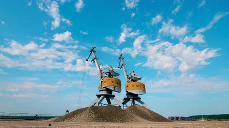 dois objetos : Two port cranes work with crushed stones, moving them in piles.