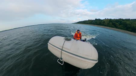 リブ : Young man sails on inflatable boat with motor.