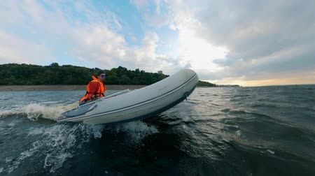 nafukovací : A man in life jacket sailing inflatable boat on water.