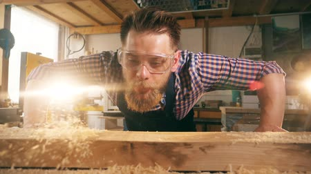 стружки : Male woodworker is blowing the shaving away in slow motion